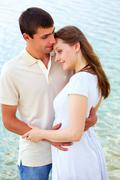Tenderness photo of peaceful couple enjoying being together with blue water on b Stock Photos