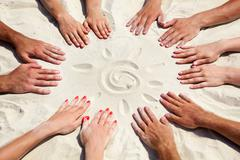 Sun in circle image of several hands on sand in the form of circle with sun in c Stock Photos