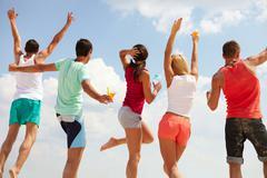 Viileä aika selän onnellinen nuori ystäviä tanssimisen beach party Kuvituskuvat