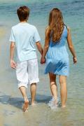 Photo of serene couple walking in water on summer vacation Stock Photos