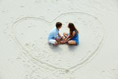 photo of happy couple sitting on sand in the center of heart - stock photo