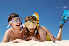 portrait of cheerful couple in aqualungs lying on sand - stock photo