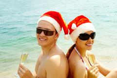 portrait of attractive couple in santa caps and sunglasses looking at camera on - stock photo