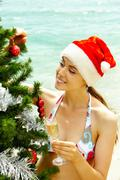 Portrait of female in bikini and santa cap holding champagne flute and looking a Stock Photos