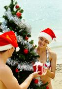 Portrait of happy couple in santa caps near xmas firtree on the beach Stock Photos