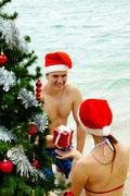 Portrait of happy man in santa cap giving giftbox to his wife near xmas firtree Stock Photos
