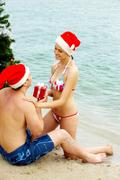 Portrait of happy woman in santa cap giving giftbox to her husband near xmas fir Stock Photos