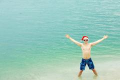 portrait of happy man in santa cap, sunglasse and swimwear raising arms and look - stock photo