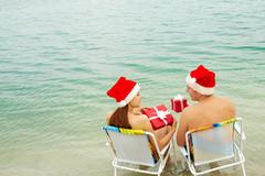 Portrait of happy couple in santa caps holding giftboxes and looking at one anot Stock Photos