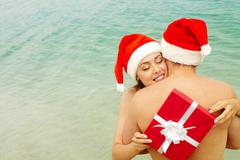 Portrait of happy female in santa cap embracing her husband while holding giftbo Stock Photos