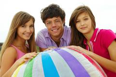 photo of happy teenage friends with ball looking at camera - stock photo