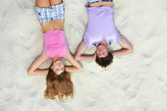 Stock Photo of above angle of teenage couple having rest on sandy beach