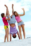 portrait of laughing teenage friends having fun on sandy beach - stock photo