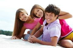 portrait of three teenage friends on sandy beach - stock photo