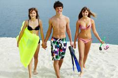 Two girls in bikini and happy guy walking down the beach Stock Photos