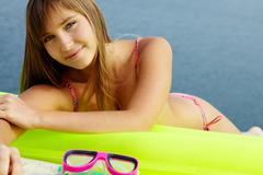 Portrait of teenage girl in bikini lying on mattress and sunbathing Stock Photos