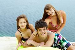 portrait of three teenage friends spending time by seaside - stock photo