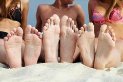 Soles of teenagers sunbathing on sandy beach Stock Photos