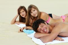 portrait of three teenage friends lying on the beach and sunbathing - stock photo