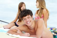 Portrait of teenage guy lying on the beach and sunbathing with two girls behind Stock Photos
