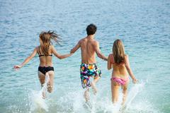 Photo of teenagers running in water while holding each other by hands Stock Photos