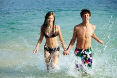 photo of teenage couple running in water while holding each other by hands - stock photo