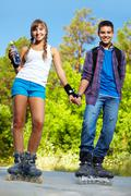 Couple of happy teens on roller skates looking at camera outside Stock Photos