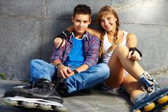 Couple of happy teens on roller skates looking at camera Stock Photos