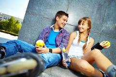 Couple of happy teens with apples chatting outside Stock Photos