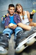 couple of two happy teens with apples sitting outside - stock photo