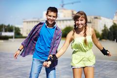 Couple of two happy roller skaters looking at camera outside Stock Photos