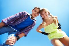 couple of two happy roller skaters looking at camera against blue sky - stock photo
