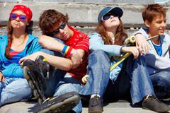 Row of several teens relaxing outside Stock Photos