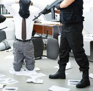 photo of kneeling businessman wearing black sacks on head with burglar standing - stock photo