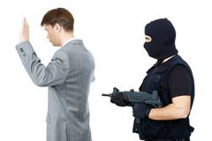 victim standing with hands raised while mafia representative pointing gun at the - stock photo