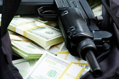 close-up of black weapon lying on heap of hundred dollar bills - stock photo
