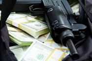 Stock Photo of close-up of black weapon lying on heap of hundred dollar bills