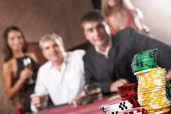 Image of different chips with people staking on background Stock Photos