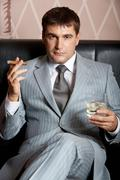 portrait of handsome man in grey suit sitting on leather sofa with whisky and ci - stock photo