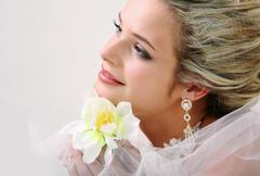 Portrait of pretty bride holding bright flower Stock Photos