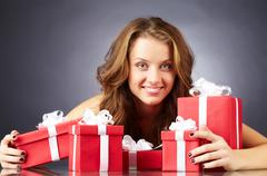 portrait of a girl with giftboxes looking at camera and smiling - stock photo