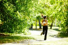 Stock Photo of a young girl jogging in the park along trees