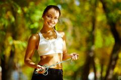 A young woman holding a skipping rope, looking at camera and smiling against nat Stock Photos