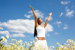 Image of happy female standing with raised arms on summer day Stock Photos