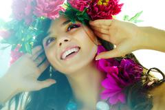 Stock Photo of beautiful woman with bright flowers in good mood