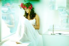 Beautiful woman in white dress sitting on window sill and looking through glass Stock Photos