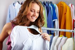A girl choosing a t-shirt in the shop Stock Photos
