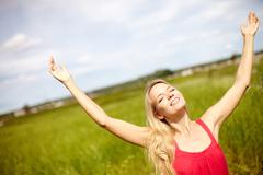 image of happy female with raised arms enjoying summer day - stock photo