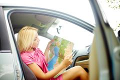 Photo of elegant woman sitting in car and looking at map Stock Photos