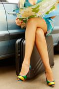 Photo of nice legs of elegant woman sitting on suitcase by her car and searching Stock Photos